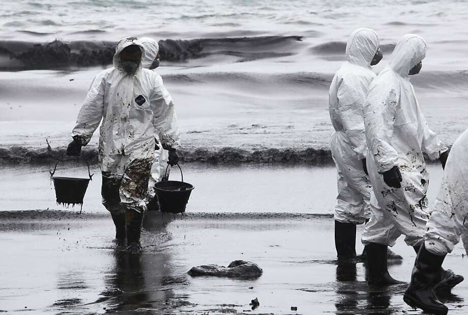 Workers use buckets to remove crude oil during a clean up operation on the beach of Prao Bay on Samet Island in Rayong province eastern Thailand Tuesday, July 30, 2013. About 50,000 liters (13,200 gallons) of crude oil that leaked from a pipeline operated by PTT Global Chemical Plc, has reached the popular tourist island in Thailand's eastern sea despite continuous attempts to clean it up.  (AP Photo) Photo: Associated Press