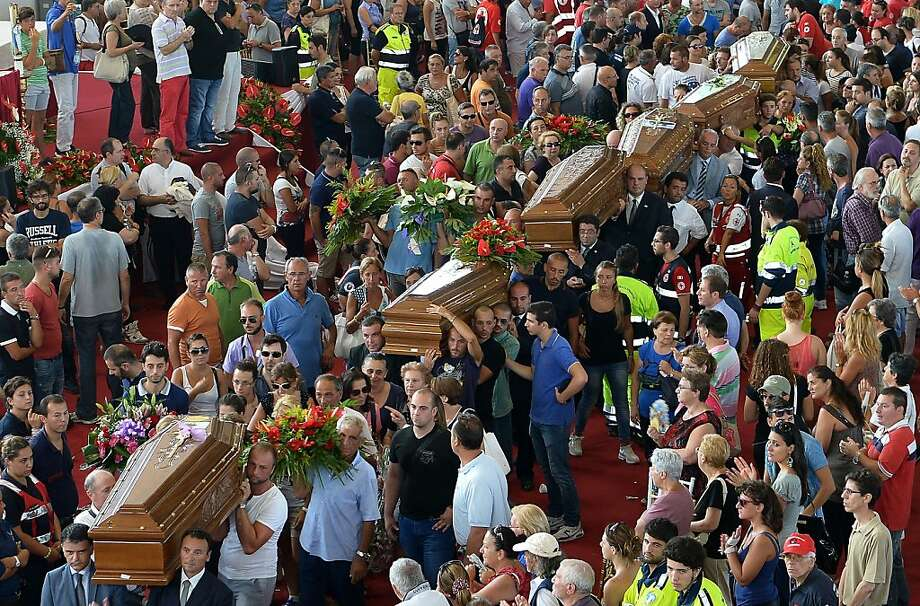 Coffins are carried by relatives after a mass funeral for the 38 people killed in Italy when a coach plunged off a viaduct near Naples on July 30, 2013, in Moteruscello, southern Italy. The coach, carrying 48 people including children, rammed several cars after failing to break on a bend, smashing through a crash barrier and off the viaduct to plunge 30 metres (98 feet) down. Prosecutors have launched an investigation into possible manslaughter over the accident, the worst such crash in western Europe in the last decade. AFP PHOTO / ALBERTO PIZZOLIALBERTO PIZZOLI/AFP/Getty Images Photo: Alberto Pizzoli, AFP/Getty Images