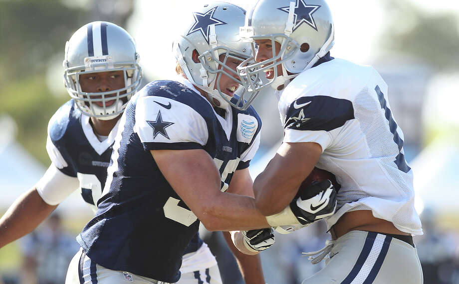 Linebacker Sean Lee (left) attempts to punch the ball out of receiver Austin Mile's arms during the afternoon session of the 2013 Dallas Cowboys training camp on Tuesday, July 30, 2013 in Oxnard. Photo: Kin Man Hui, San Antonio Express-News / ©2013 San Antonio Express-News