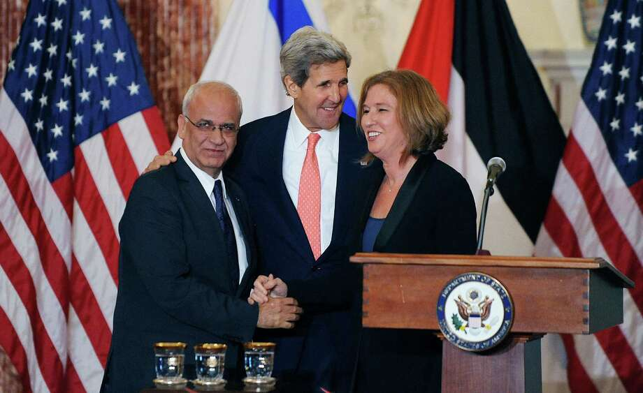 Secretary of State John Kerry (center) watches as Israeli Justice Minister Tzipi Livni (right) and Palestinian chief negotiator Saeb Erekat shake hands during a news conference after the start of peace talks in Washington. Photo: Olivier Douliery / McClatchy