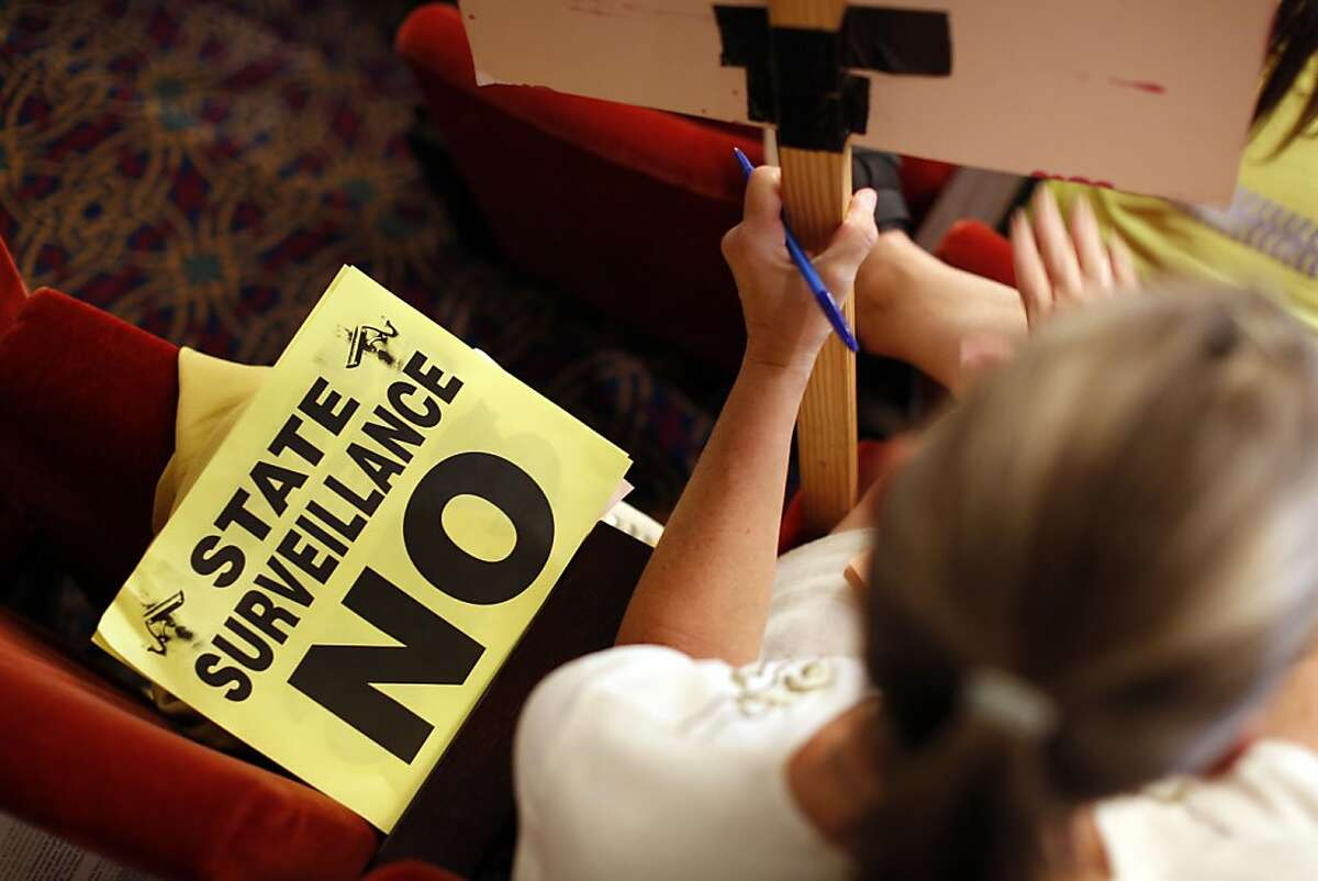 A sign protesting the Domain Awareness Center sits next to a woman during a city council meeting at the Oakland City Hall in Oakland, Calif. on July 30, 2013.