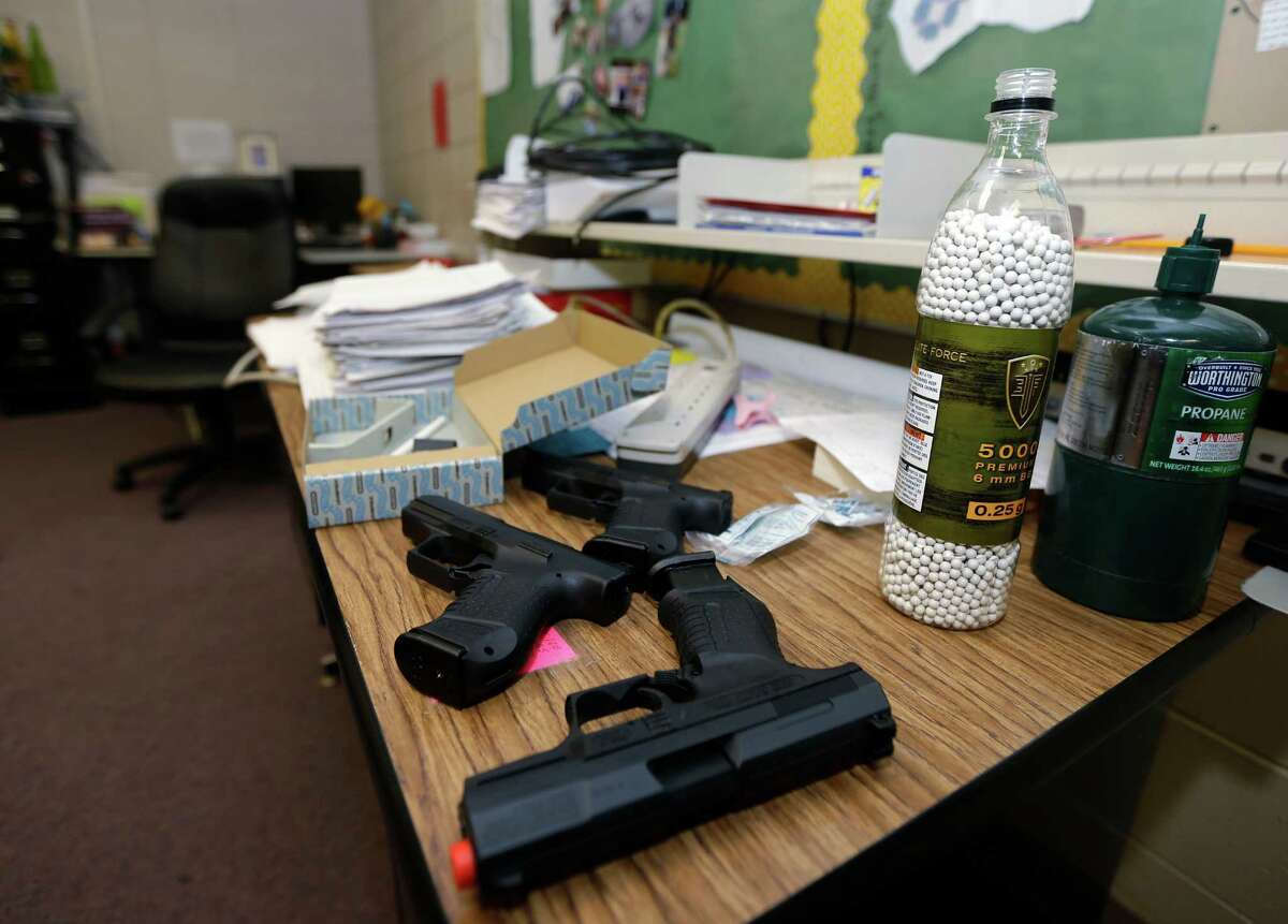 In this photo taken July 11, 2013, practice air-powered handguns sit on a teacher's desk in a classroom at Clarksville High School in Clarksville, Ark. Twenty Clarksville School District staff members are training during the summer to be armed security guards on campus. (AP Photo/Danny Johnston) ORG XMIT: ARDJ204