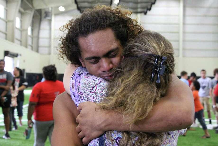 Fua Sapoi hugs a teacher at a memorial service Tuesday for former Euless Trinity students, including A&M's Polo Manukainiu. Photo: Uriel J. Garcia / Associated Press