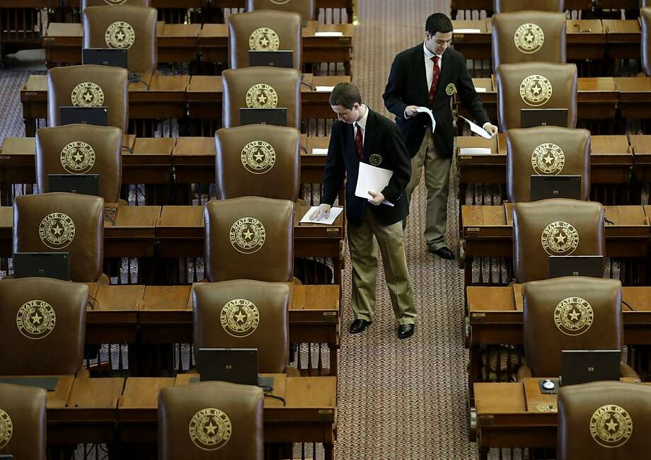 Aides place papers on the desks of House members as they prepare the Chamber for the the last day of a special session, Tuesday, July 30, 2013, in Austin, Texas. The Texas House failed to approve a constitutional amendment to boost funding for roads and bridges Monday, possibly triggering a third special session. (AP Photo/Eric Gay) Photo: Eric Gay, Associated Press