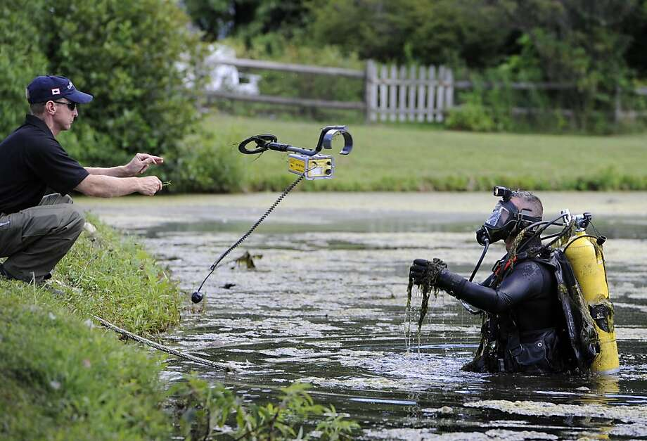A member of the Connecticut State Police Dive Team throws a metal detector to a diver in the water as they continue to search Pine Lake for the second day, Tuesday July 30, 2013, in Bristol, Conn.  Bristol, Conn., is the hometown of former New England Patriots football player Aaron Hernandez.  Authorities have declined to comment on the search except to confirm it is related to the Hernandez investigation.   (AP Photo/Jessica Hill) Photo: Jessica Hill, Associated Press