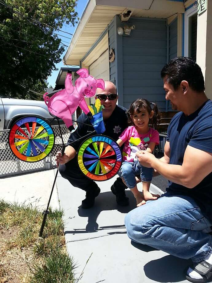 Newark girl Jasmine, 7, receives a replacement for the whirligig that was stolen from her front lawn. Photo: -, Newark Police Department