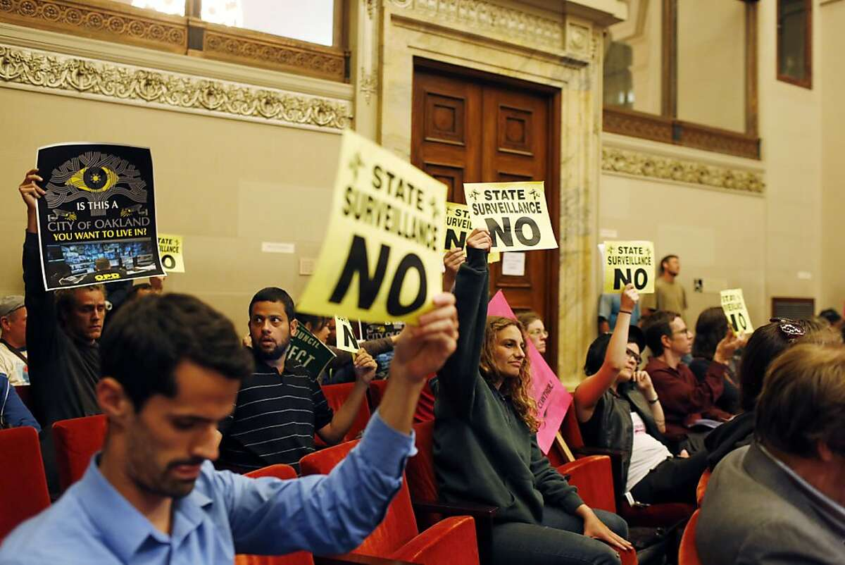 Protestors against the Domain Awareness Center hold up signs during a city council meeting.