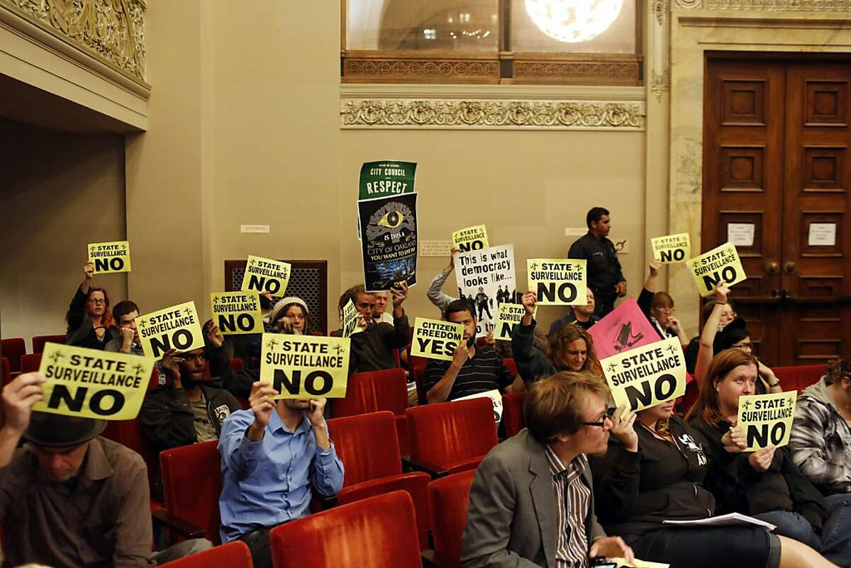 Protestors against the Domain Awareness Center hold up signs during a city council meeting at the Oakland City Hall in Oakland, Calif. on July 30, 2013.