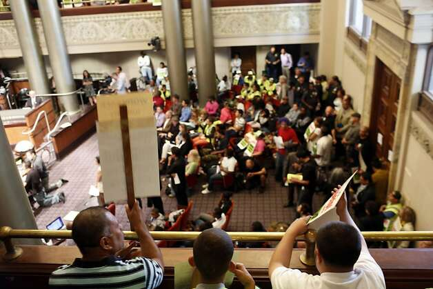 Audience members hold up picket signs during a city council meeting at the Oakland City Hall in Oakland, Calif. on July 30, 2013. Photo: Ian C. Bates, The Chronicle