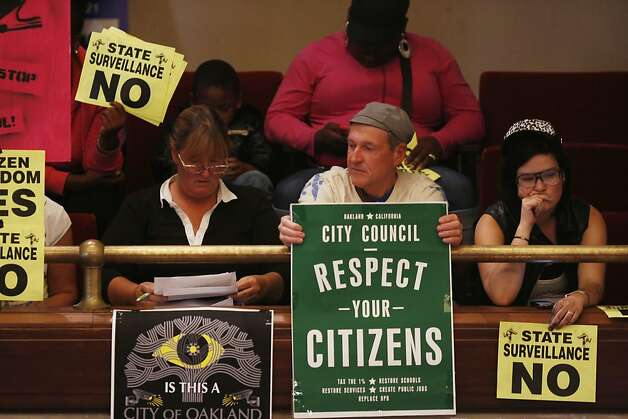 Audience members hold signs protesting the Domain Awareness Center during a city council meeting at the Oakland City Hall in Oakland, Calif. on July 30, 2013. Photo: Ian C. Bates, The Chronicle