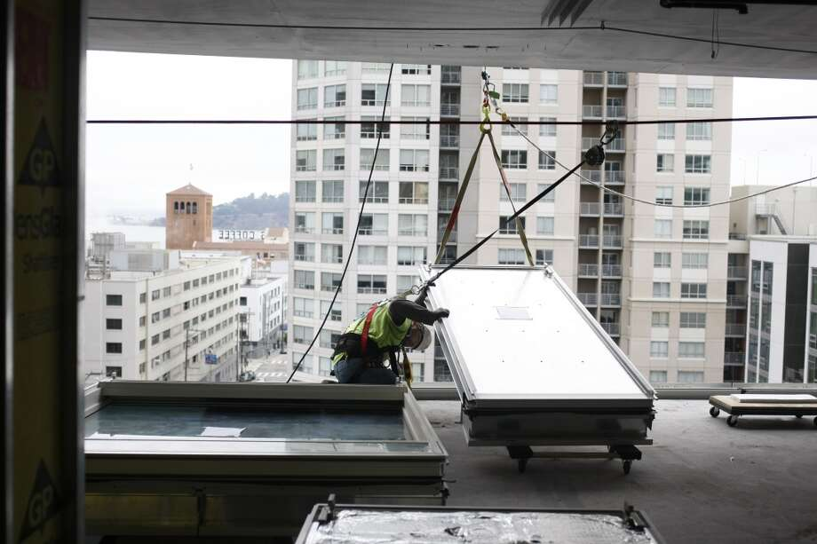 Gerardo Gonzalez, a glass install foreman, works to install a Type B Aluminum Panel in the under-construction One Rincon Hill Phase Two on July 25, 2013 in San Francisco, Calif. Photo: Pete Kiehart, The Chronicle