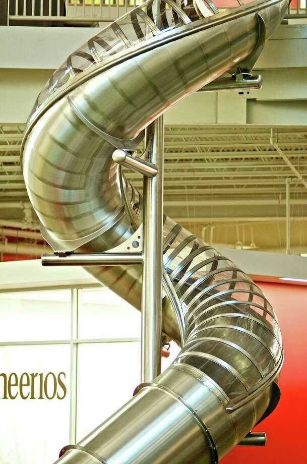 A stainless silver slide tube connects the first and the second floors of Rackspace. Photo: Courtesy Photo