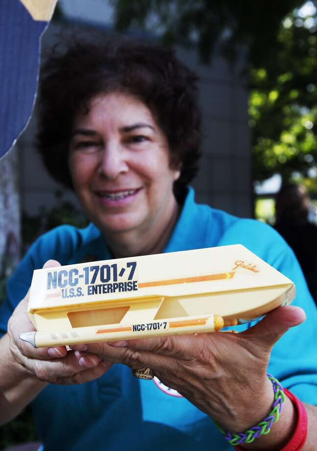 "Candy Torres holds a model of the 1967 Galileo ship as she waits to enter the Space Center Houston to see the unveiling of the fully-restored StarTrek Galileo ship. Officials unveiled the newly restored spaceship prop featured in the 1967 Star Trek episode ""The Galileo Seven"" after a yearlong restoration project led by Adam and Leslie Schneider, die-hard Star Trek fans and memorabilia collectors. The life-size spaceship will be on permanent display inside Space Center Houston's Zero-G Diner and will be one of only a few exhibitions in the world where visitors can see iconic sci-fi history that has influenced generations of innovators. (Cody Duty / Houston Chronicle) Photo: Cody Duty, Houston Chronicle"
