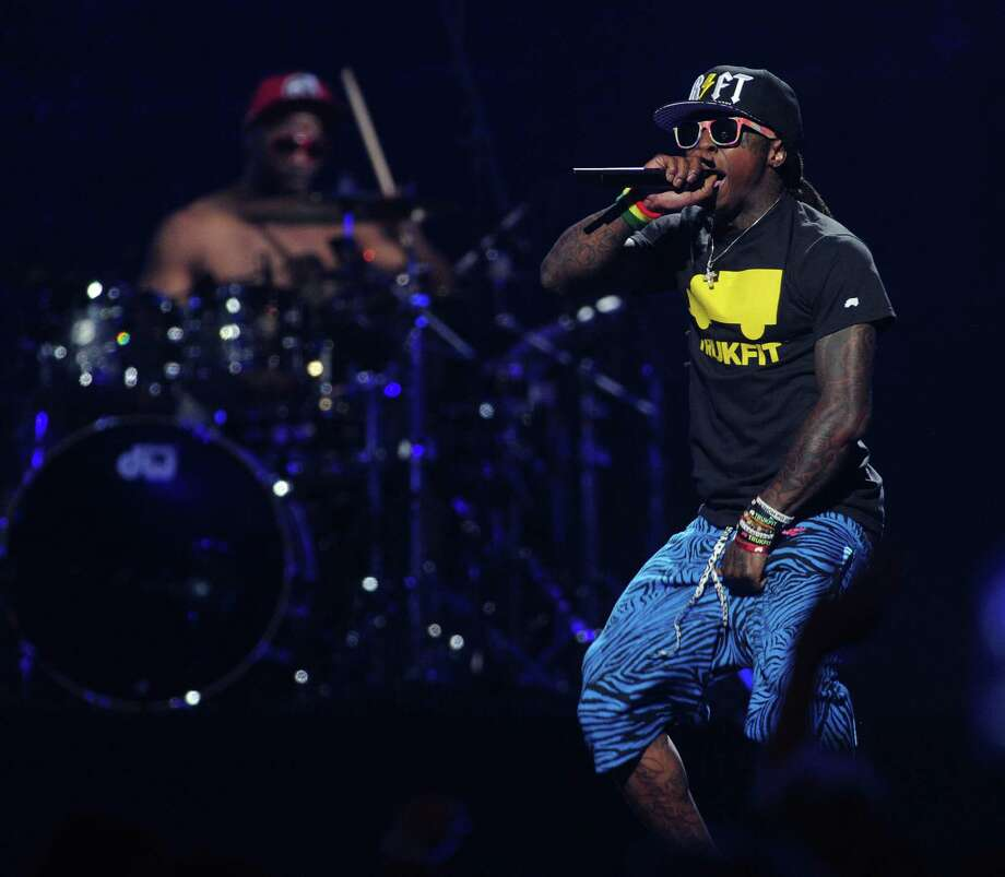 FILE - In this Sept. 21, 2012 file photo, Lil Wayne performs at the iHeart Radio Music Festival at the MGM Grand Arena in Las Vegas. Lil Wayne and Rick Ross, two of the most celebrated and successful artists in rap today, recently lost major endorsements after protests forced high profile corporations to drop the rap stars. Both artists rapped lyrics deemed vulgar and over-the-top; one referring to rape, the other about the beating of Emmett Till, on songs where they were the featured acts. (Photo by Eric Reed/Invision/AP, File) ORG XMIT: CAENT992 Photo: Eric Reed / Invision