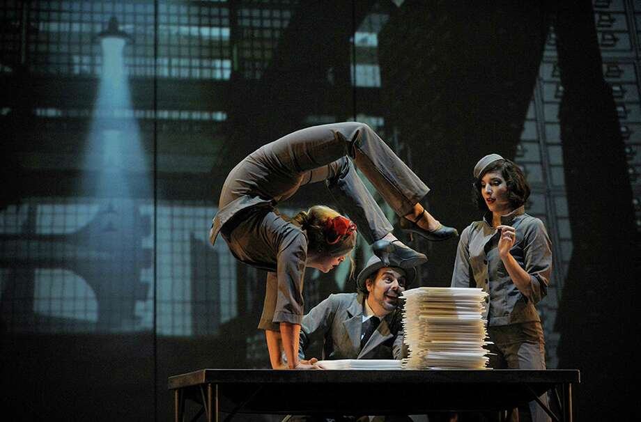 One man?s imagination transforms piles of papers, looming towers, and giant gears into a vibrant, romantic, and lavish cityscape. Lauren Herley, Ashley Carr, Myriam Deraiche perform. (Courtesy Cirque Eloize) Photo: VALERIE'REMISE