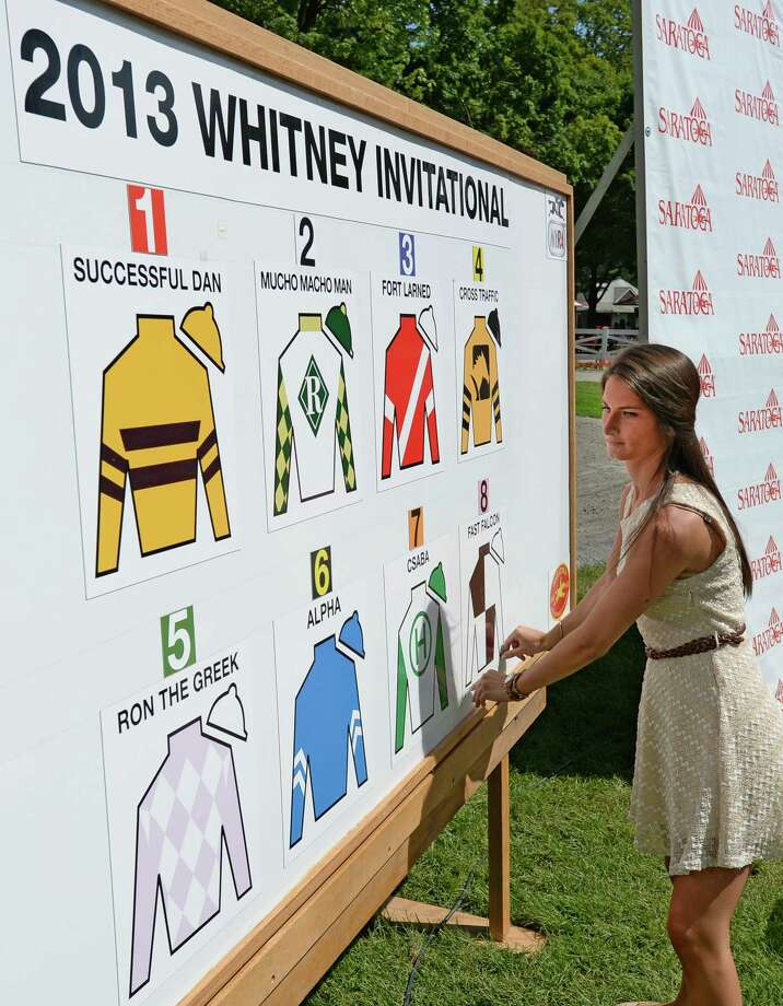 Teal Albertrani of NYRA places the colors of the entrants for the 2013 Whitney Invitational on the post position board Wednesday morning, July 31, 2013 at Saratoga Race Course in Saratoga Springs, N.Y.     (Skip Dickstein/Times Union) Photo: SKIP DICKSTEIN