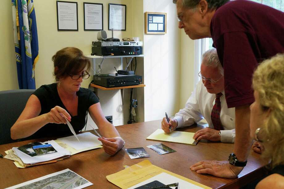 Faith Ricciotti, left, shows photographs of the view of the Interstate 95 rest area from her Papermill Lane home during a meeting with neighbors and FIrst Selectman Mike Tetreau. Photo: Genevieve Reilly / Fairfield Citizen