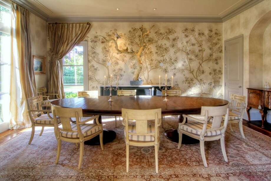The spacious Dining Room with delicately wrought Gracie wallpaper has floor to ceiling windows that allow great views of the front yard.