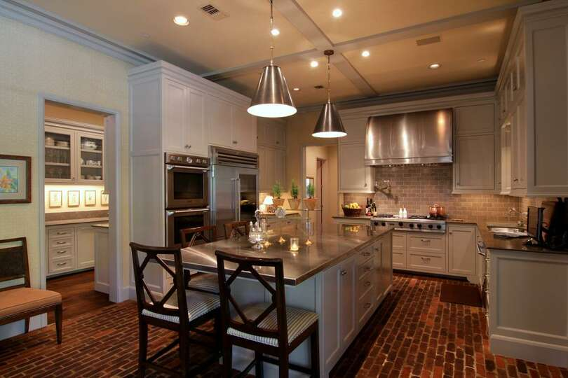 The kitchen has rustic cedar bayou half brick floors and for Kitchen island houston
