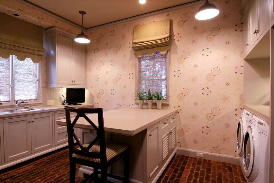 The Laundry Room / Project Room which also has Cedar Bayou half-brick floors, features a convenient and spacious folding station. Several windows allow for a lot of natural light.