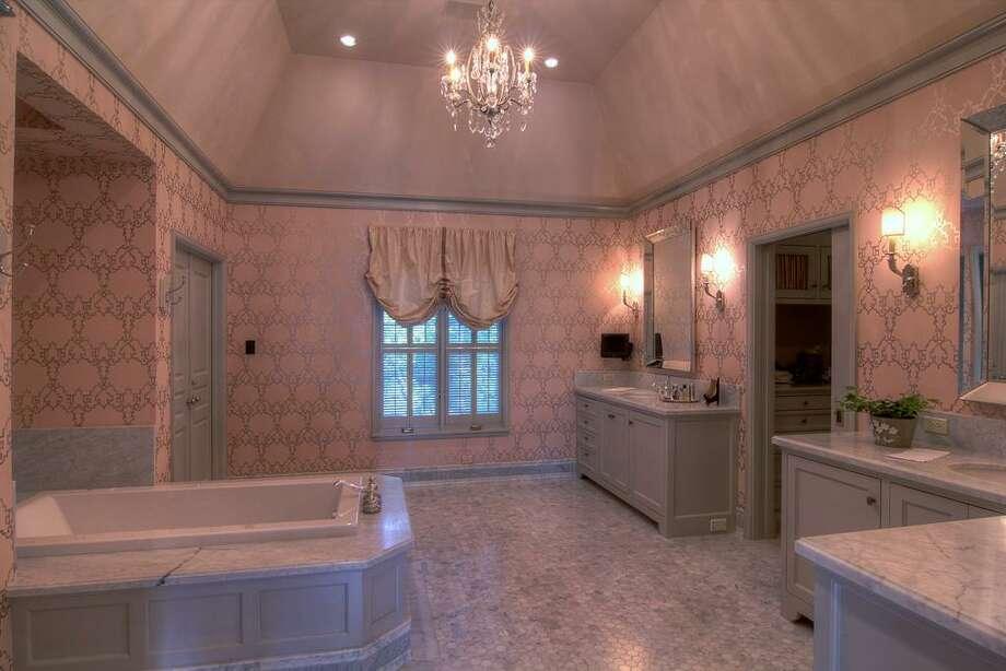 The exquisite Master Bathroom features Carrara marble countertops, shower, tub surround and splash, and Carrara marble hexagonal tile flooring.
