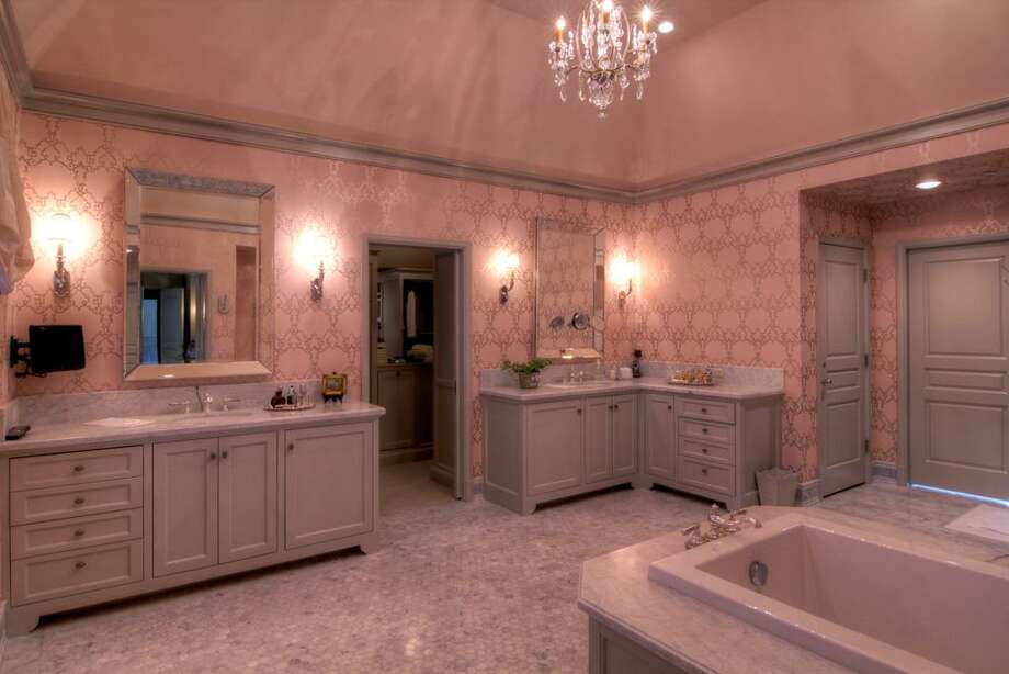The Master Bathroom has Bain Utra tub, designer wallpaper, a concealed coffee bar with under-counter refrigerator and dual walk-in closets with customized storage.