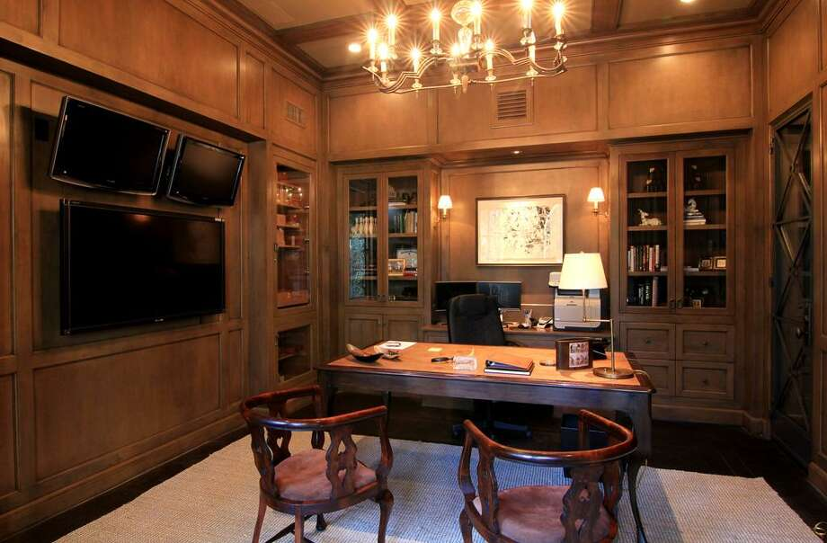 The Office features dark hardwood floors, rich wood paneling and glass-front book and display cabinets. The door on the right opens to the wine cellar. To the left, the built-in humidor.