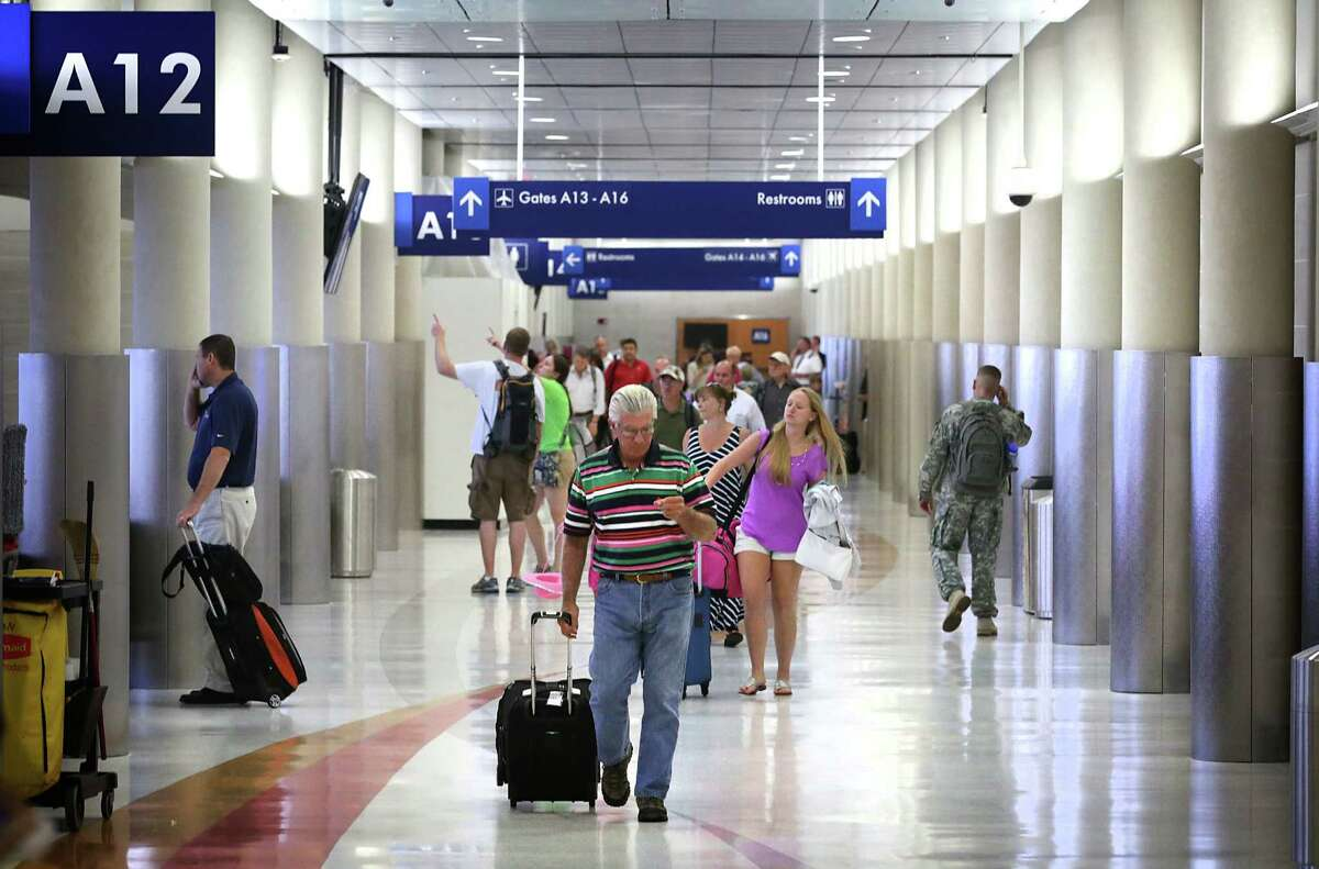 Travelers walk down a renovated corridor after arriving at the San Antonio International Airport. Renovations are ongoing at Terminal A of the San Antonio International Airport, on Tuesday, July 30, 2013.