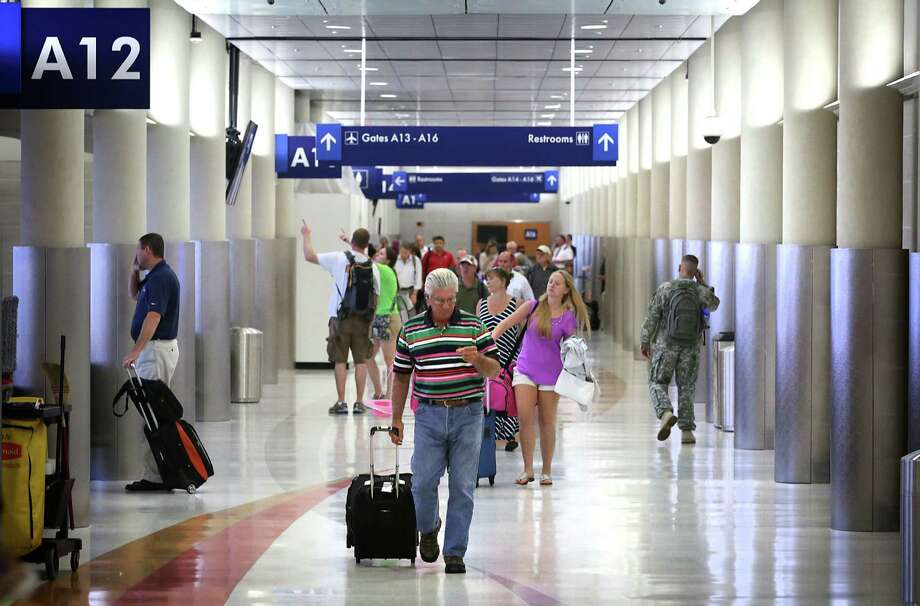 Travelers walk down a renovated corridor after arriving at the San Antonio International Airport. Renovations are ongoing at Terminal A of the San Antonio International Airport, on Tuesday, July 30, 2013. Photo: Bob Owen, San Antonio Express-News / © 2012 San Antonio Express-News
