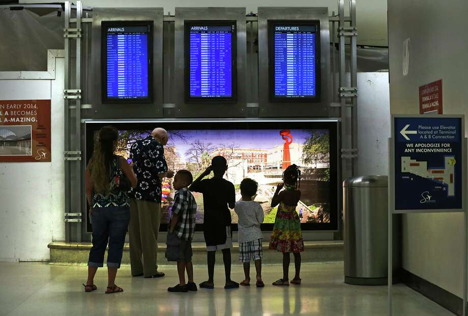 People read the arrival boards in Terminal A where renovations are ongoing at the San Antonio International Airport, on Tuesday, July 30, 2013. Photo: Bob Owen, San Antonio Express-News / © 2012 San Antonio Express-News