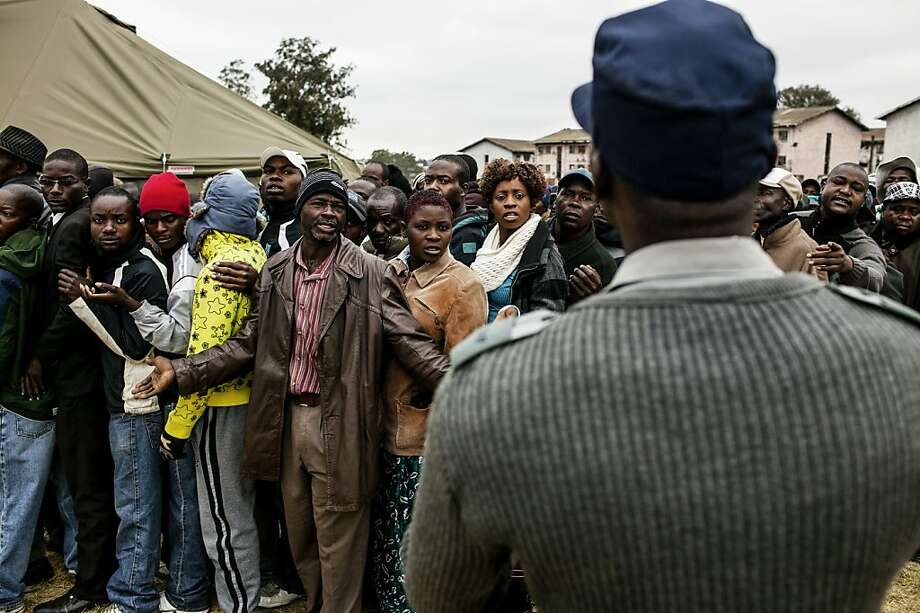 Voters waiting to cast ballots in the Zimbabwe election complain to police officers about the slow pace of the lines. Morgan Tsvangirai is challenging longtime president Robert Mugabe. Photo: Pete Muller, New York Times
