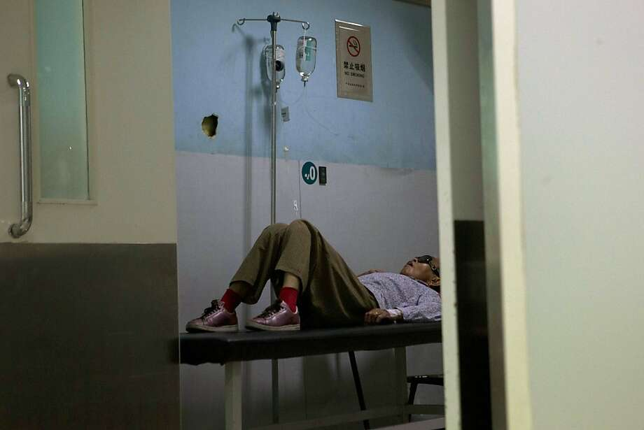 A patient rests in a ward at a hospital in Beijing, China, Wednesday, July 31, 2013.  Low salaries and skimpy budgets drive doctors, nurses and administrators to make ends meet by accepting money from patients, drug suppliers and others. Accusations this month that GlaxoSmithKline employees bribed Chinese doctors to prescribe its drugs brought international attention to the flow of illicit money. But to China's public, the practice has long been common knowledge.(AP Photo/Ng Han Guan) Photo: Ng Han Guan, Associated Press