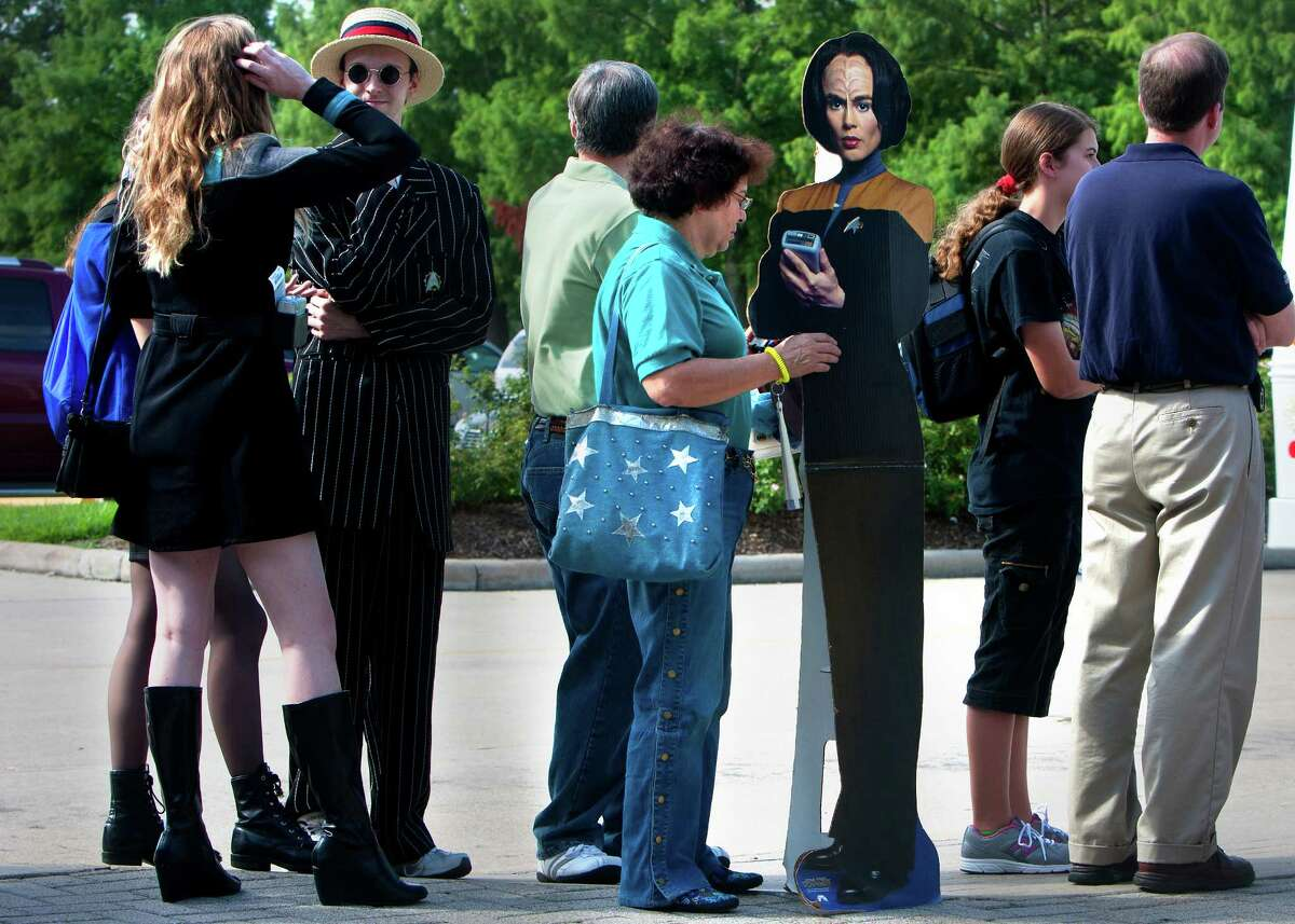 """Candy Torres carries a cut-out of Star Trek character, B'Elanna Torres, as she waits in line for the unveiling of the 1967 Star Trek Galileo ship at the Space Center Houston, Wednesday, July 31, 2013, in Houston. Featured in the 1967 Star Trek episode """"The Galileo Seven,"""" the ship made its debut at the Space Center Houston after a year-long restoration project led by Adam and Leslie Schneider, die-hard Star Trek fans and memorabilia collectors. The life-size spaceship will be on permanent display inside Space Center Houston's Zero-G Diner and will be one of only a few exhibitions in the world where visitors can see iconic sci-fi history that has influenced generations of innovators."""