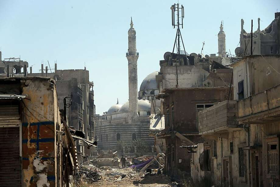 A government tankrolls through the ruins of Homs, Syria, near the Khaled bin Walid 