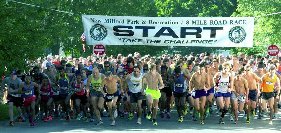The field of nearly 600 runners and walkers responds to the starter's gun just after 9 a.m. on Saturday to kick off the 46th annual New Milford 8-mile and 11th annual Village Fair Days 5K road races. Side by side to the left are eventual 8-mile champions Mengistu Nebsi (7) and Aziza Aliyu (422) of Ethiopia. Among those directly under the banner are former New Milford resident George Adams (406), who finished 14th, Mike Nahom (429) of New Milford, who finished 10th, fifth-place finisher Jake Feinstein of Newtown, 11th-place Ryan Clarke (10) of New Milford and upcoming New Milford High senior Zach Guptill (244), who claimed 23rd place. Photo: Trish Haldin