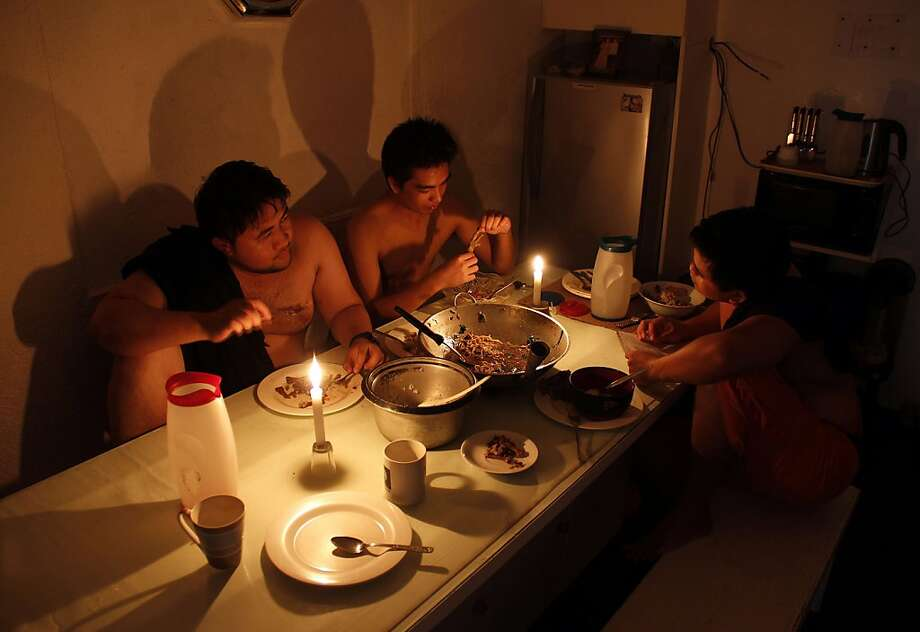 A family uses candles for light as they eat in Legazpi City in Albay province, southeast of Manila, after a power cooperative was unable to pay its bill and the Philippine Department of Energy cut off power for more than a day. About 160,000 households were affected. Photo: Charism Sayat, AFP/Getty Images