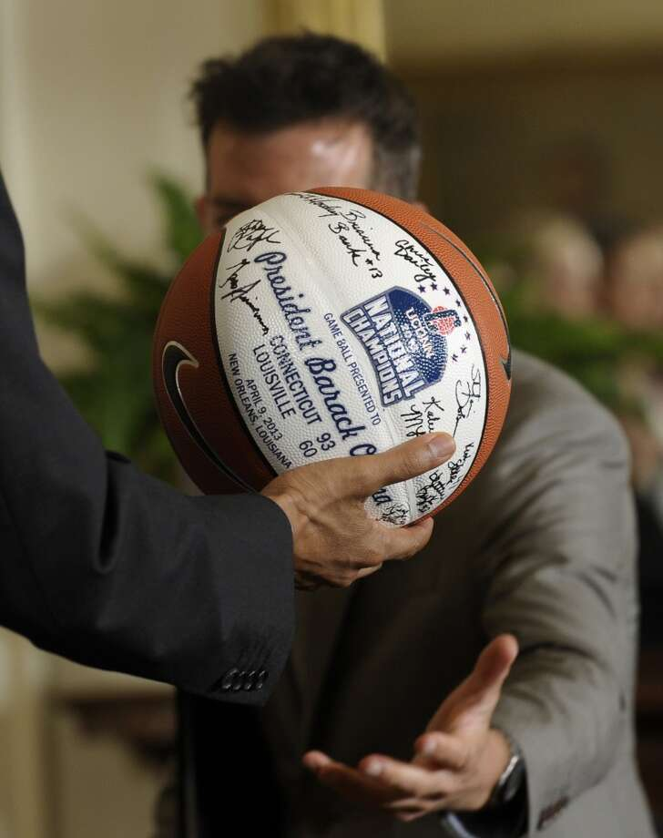 President Barack Obama passes over the ball he was presented with during an event to honor the 2013 NCAA Women's Basketball Champion team, the University of Connecticut Huskies, in the East Room of the White House in Washington, Wednesday, July 31, 2013. (AP Photo/Susan Walsh) Photo: Associated Press