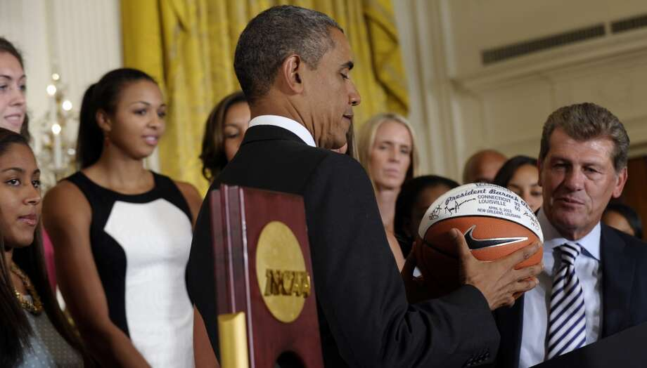 President Barack Obama looks at the basketball that he was given during a ceremony to honor the 2013 NCAA Women's Basketball Champion team, the University of Connecticut Huskies, Wednesday, July 31, 2013,  in the East Room of the White House in Washington, Wednesday, July 31, 2013. UConn head basketball coach Geno Auriemma watches at right. (AP Photo/Susan Walsh) Photo: Associated Press