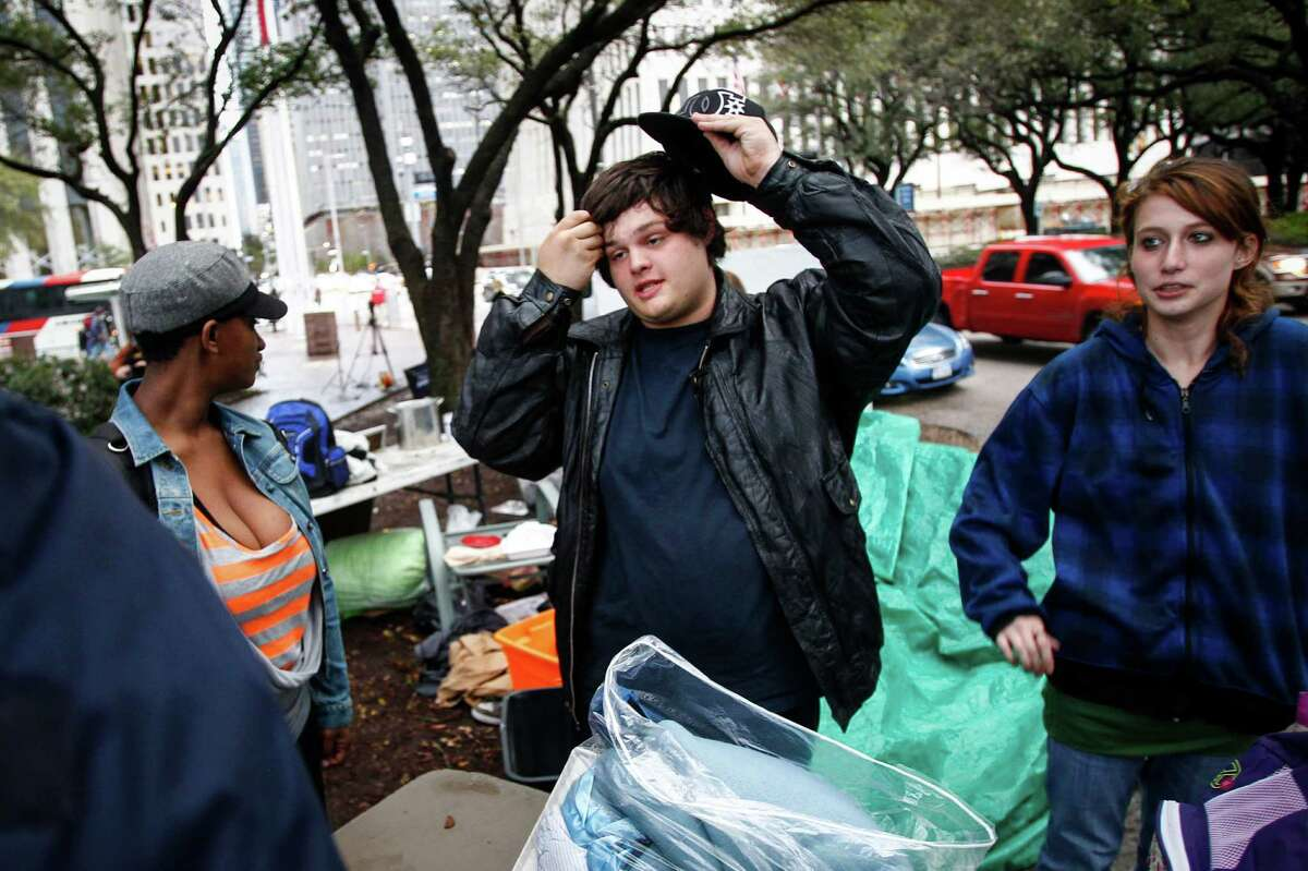 """Justin Meeker (center) and other participants in the Occupy Houston movement pack up their belongings at Tranquility Park before police officers moved in and took over the park after sunset on Mayor Annise Parker's orders, Monday, Feb. 13, 2012, in Houston. The move comes approximately four months after Occupy Houston movement began. """"I told Occupy Houston leaders in January they need to decide the next phase for their effort,"""" said Mayor Annise Parker. """"I support their right to free speech and I'm sympathetic to their call for reform of the financial system, but they can't simply continue to occupy a space indefinitely. We have to get the area ready for the spring festivals and that necessitates their leaving."""" ( Michael Paulsen / Houston Chronicle )"""