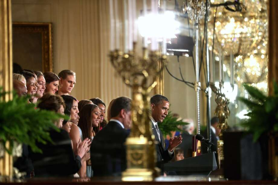 WASHINGTON, DC - JULY 31:  President Barack Obama (R) is reflected in a mirror in the East Room as he hosts the 2013 NCAA champion University of Connecticut Huskies Women's basketball players at the White House July 31, 2013 in Washington, DC. Obama hosted the team after they defeated the University of Louisville on April 9 to win their eighth national championship.  (Photo by Chip Somodevilla/Getty Images) Photo: Getty Images