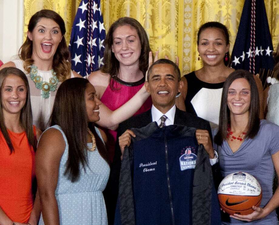 University of Connecticut Huskies teammates Stefanie Dolson, top left, and Kiah Stokes, top right, give the 'bunny ears' to President Barack Obama as he poses for photo with the team to honor their 2013 NCAA Women's Basketball Championship win, during a ceremony in the East Room of the White House, Wednesday, July 31, 2013, in Washington. Also seen top center Breanna Stewart, and from bottom left, Caroline Doty, Kaleena Mosqueda-Lewis and Kelly Faris. (AP Photo/Carolyn Kaster) Photo: Associated Press
