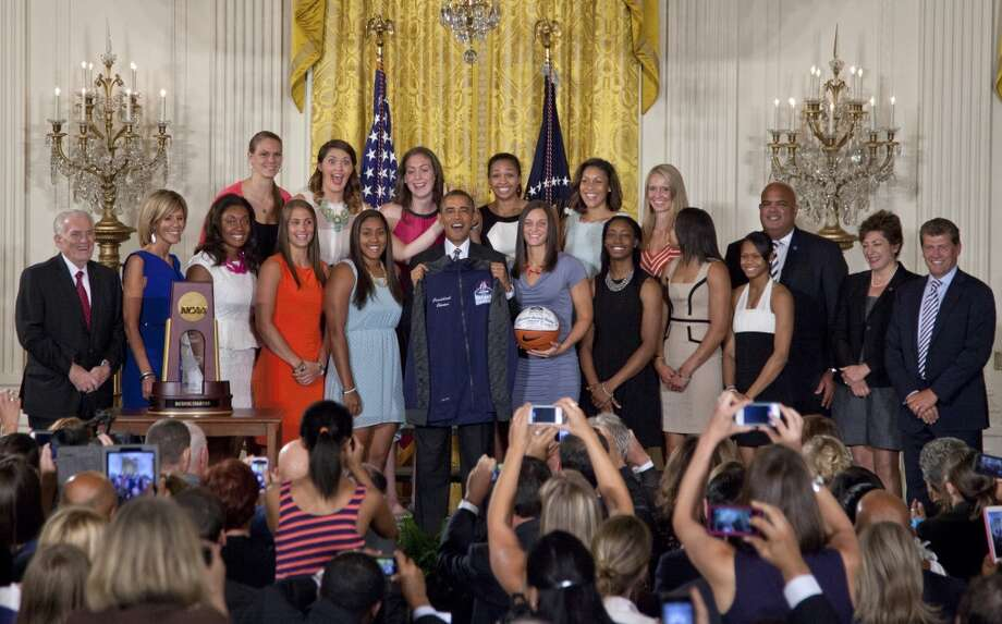 University of Connecticut Huskies basketball teammates Stefanie Dolson, top second from left, and Kiah Stokes, top fourth from left, give the 'bunny ears' to President Barack Obama as he poses for photo with the team during a ceremony in the East Room of the White House in Washington, Wednesday, July 31, 2013 where he honored their 2013 NCAA Women's Basketball Championship win. (AP Photo/Carolyn Kaster) Photo: Associated Press
