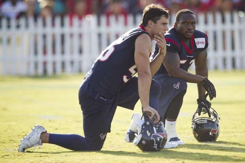 inside linebackers Brian Cushing (56) and Joe Mays (53) take a knee between drills.