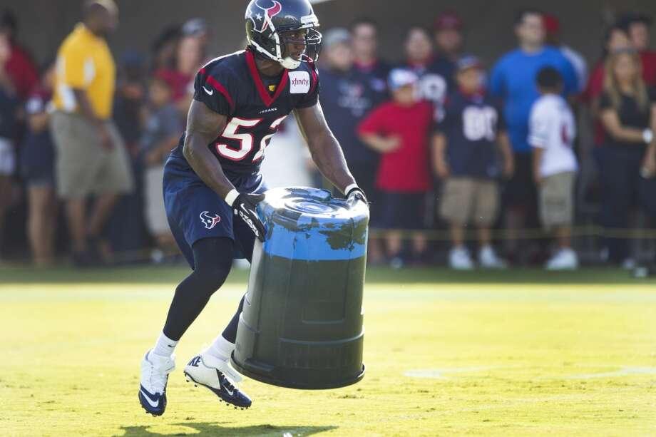 Inside linebacker Tim Dobbins grabs a trash can as he runs through a special teams drill. Photo: Brett Coomer, Chronicle