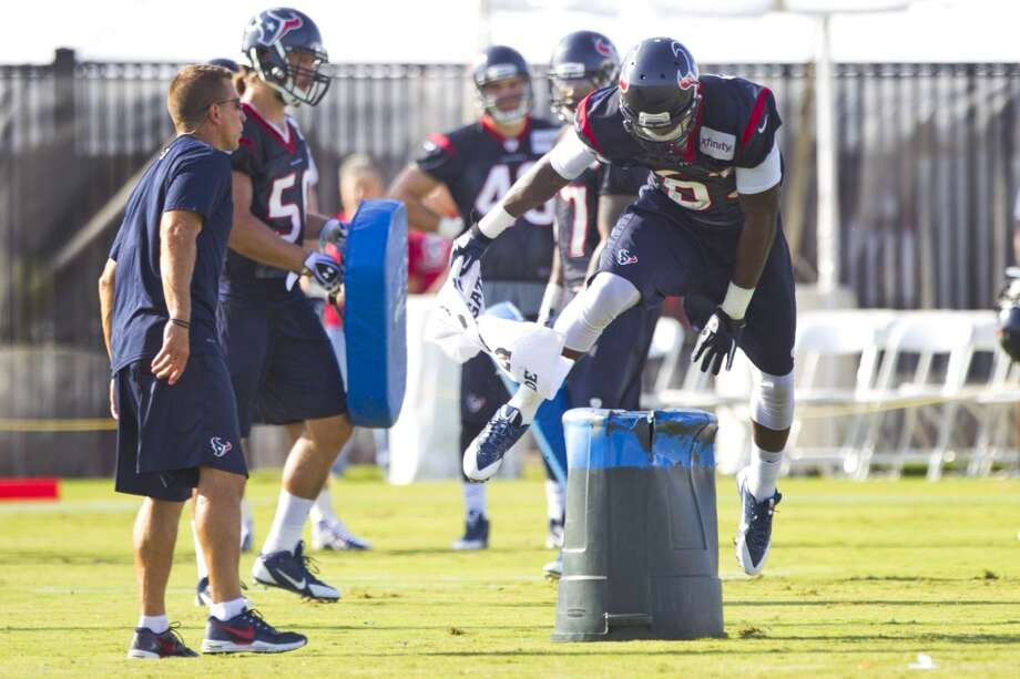 Linebacker Willie Jefferson (63) leaps over a trash can while running a special teams drill. Photo: Brett Coomer, Chronicle