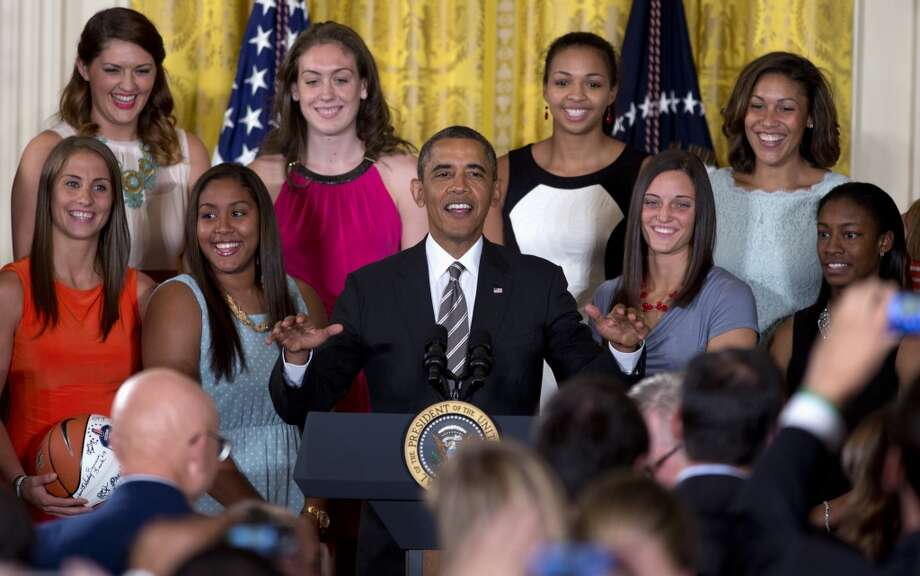 President Barack Obama gestures to the  audience to sit as he arrives for a ceremony in the East Room of the White House to honor the University of Connecticut Huskies for their 2013 NCAA Women's Basketball Championship win, Wednesday, July 31, 2013, in Washington. University of Connecticut Huskies seen from top left are, Stefanie Dolson, Breanna Stewart, Kiah Stokes and assistant coach Marisa Moseley, from bottom left, Caroline Doty, Kaleena Mosqueda-Lewis, Kelly Faris and Brianna Banks. (AP Photo/Carolyn Kaster) Photo: Associated Press