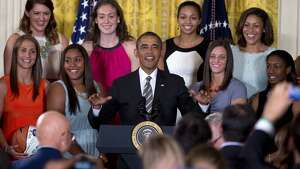 President Barack Obama gestures to the  audience to sit as he arrives for a ceremony in the East Room of the White House to honor the University of Connecticut Huskies for their 2013 NCAA Women's Basketball Championship win, Wednesday, July 31, 2013, in Washington. University of Connecticut Huskies seen from top left are, Stefanie Dolson, Breanna Stewart, Kiah Stokes and assistant coach Marisa Moseley, from bottom left, Caroline Doty, Kaleena Mosqueda-Lewis, Kelly Faris and Brianna Banks. (AP Photo/Carolyn Kaster)
