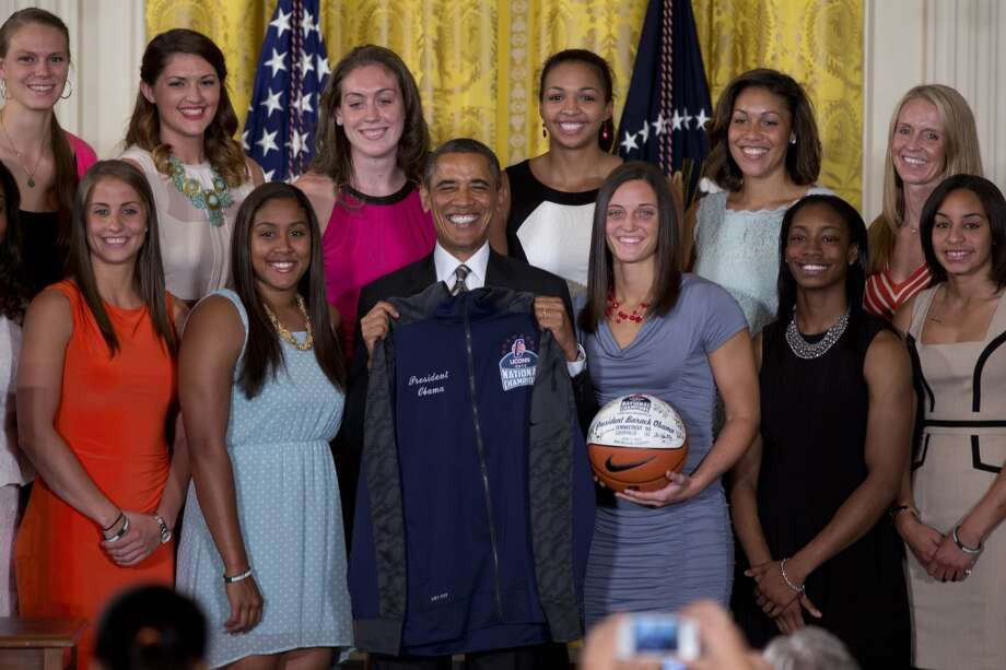 President Barack Obama poses with a jacket and an autographed ball during a ceremony in the East Room of the White House to honor the University of Connecticut Huskies for their 2013 NCAA Women's Basketball Championship win, Wednesday, July 31, 2013, in Washington. University of Connecticut Huskies seen from top left are, Heather Buck, Stefanie Dolson, Breanna Stewart, Kiah Stokes and assistant coaches Marisa Moseley and Shea Ralph, from bottom left, Caroline Doty, Kaleena Mosqueda-Lewis, Kelly Faris, Brianna Banks and Bria Hartley.  (AP Photo/Carolyn Kaster) Photo: Associated Press