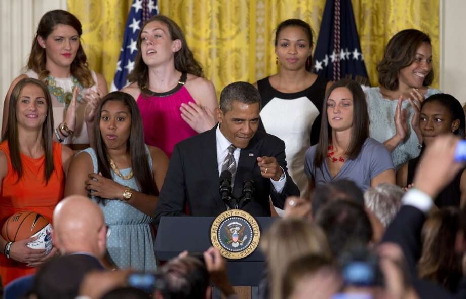 President Barack Obama points to the audience as he arrives for a ceremony in the East Room of the White House in Washington, Wednesday, July 31, 2013, to honor the University of Connecticut Huskies for their 2013 NCAA Women's Basketball Championship. University of Connecticut Huskies seen from top left are, Stefanie Dolson, Breanna Stewart, Kiah Stokes and assistant coach Marisa Moseley, from bottom left, Caroline Doty, Kaleena Mosqueda-Lewis, Kelly Faris and Brianna Banks. (AP Photo/Carolyn Kaster) Photo: Associated Press