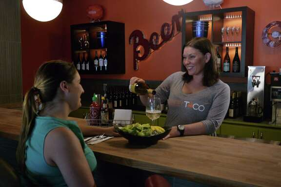 Julia Sharaby, right, serves a customer at Fusion Taco, her new downtown restaurant.